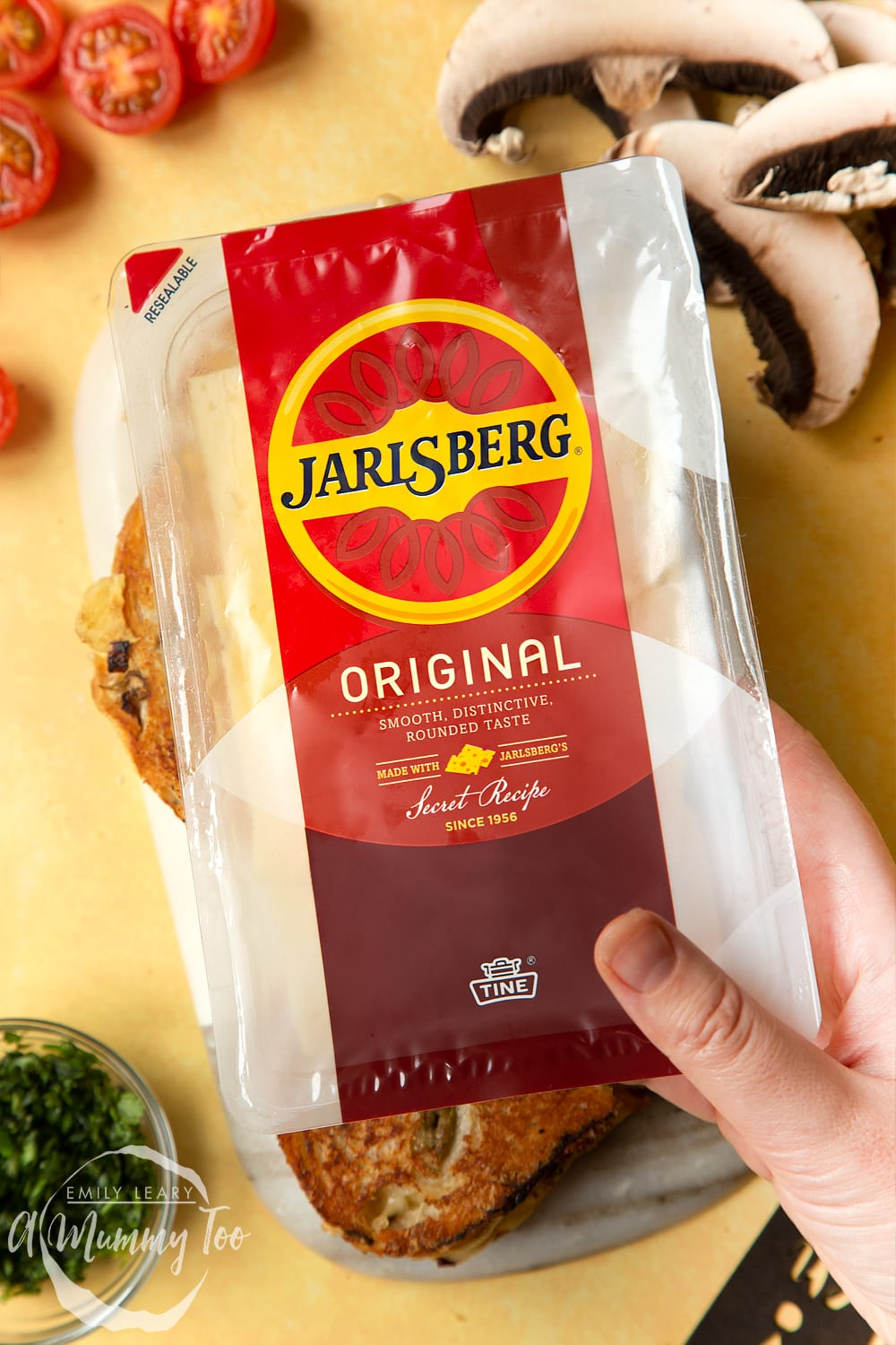 A packet of Jarlsberg cheese is being held up, two mushroom toasties are also on the table.