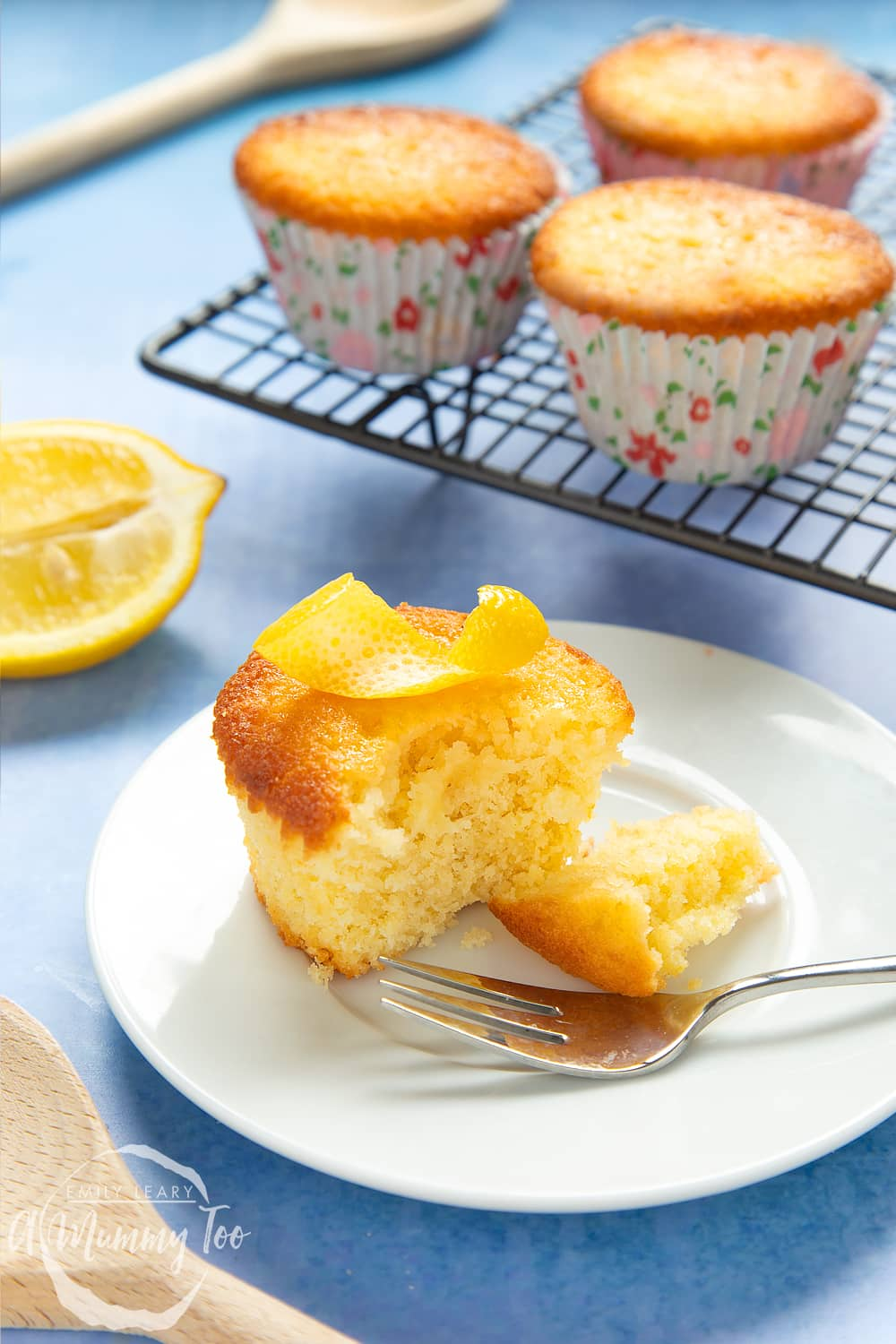 Lemon drizzle cupcake on a white plate with a cake fork. A curl on lemon ring sits on top of the cake, which has been cut open. More cakes are cooling on a rack in the background.