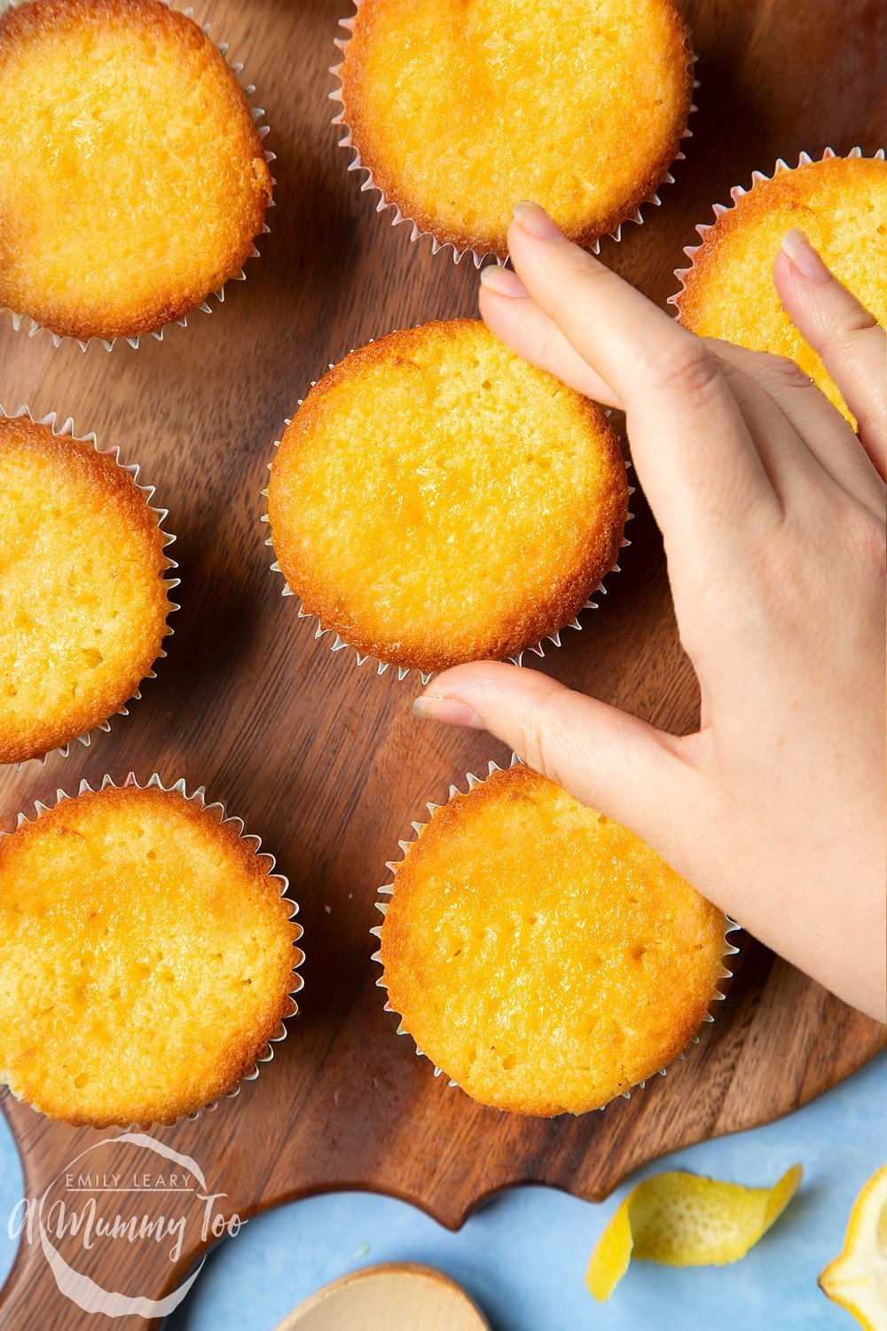 Lemon drizzle cupcakes on a wooden board. A hand reaches for one.