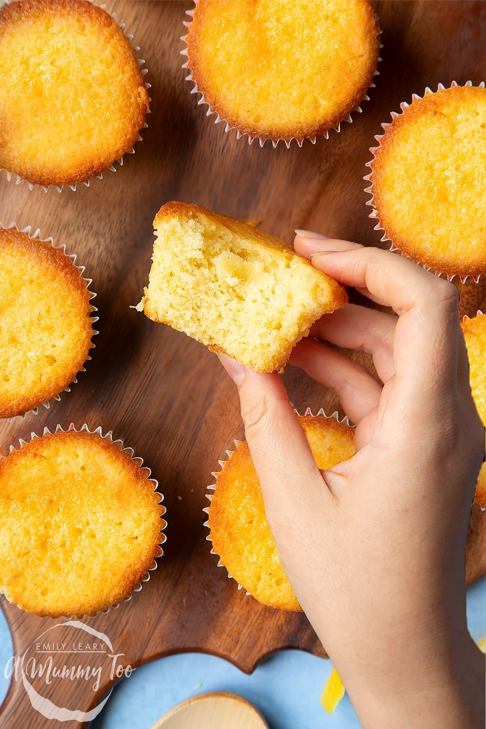 A hand holding a lemon drizzle cupcake with a bite taken out of it. More cupcakes sit on a wooden board in the background.
