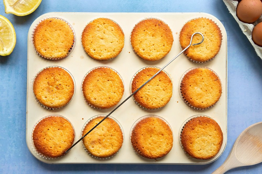 Lemon drizzle cupcakes in a cream-coloured muffin tray. Holes have been poked into the cupcakes with a skewer.