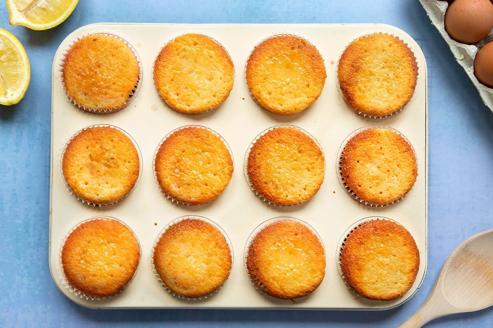 Lemon drizzle cupcakes in a cream-coloured muffin tray.