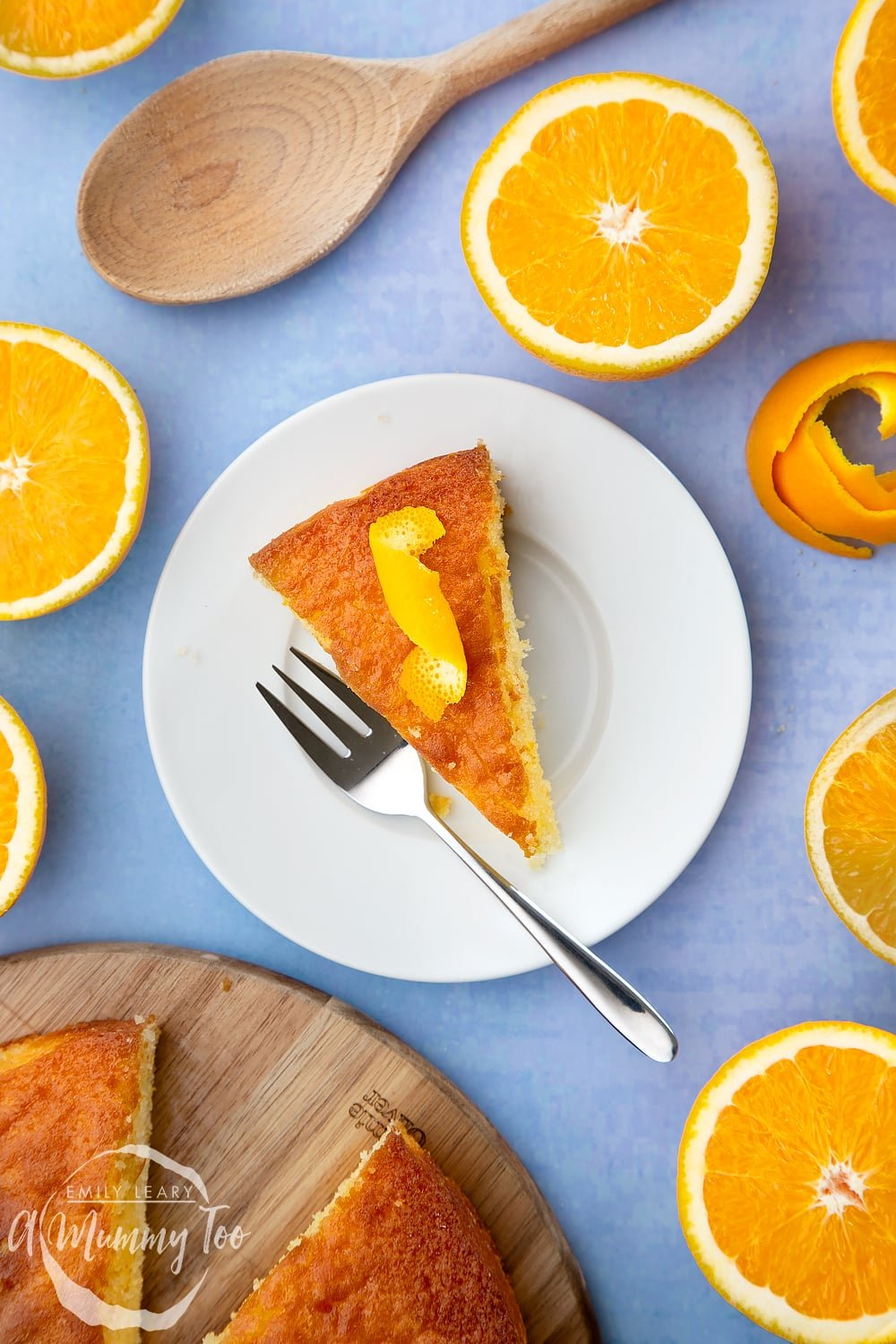 A slice of orange drizzle cake served on a small white plate. A curl of orange peel sits on top of the cake. A cake fork rests on the plate.