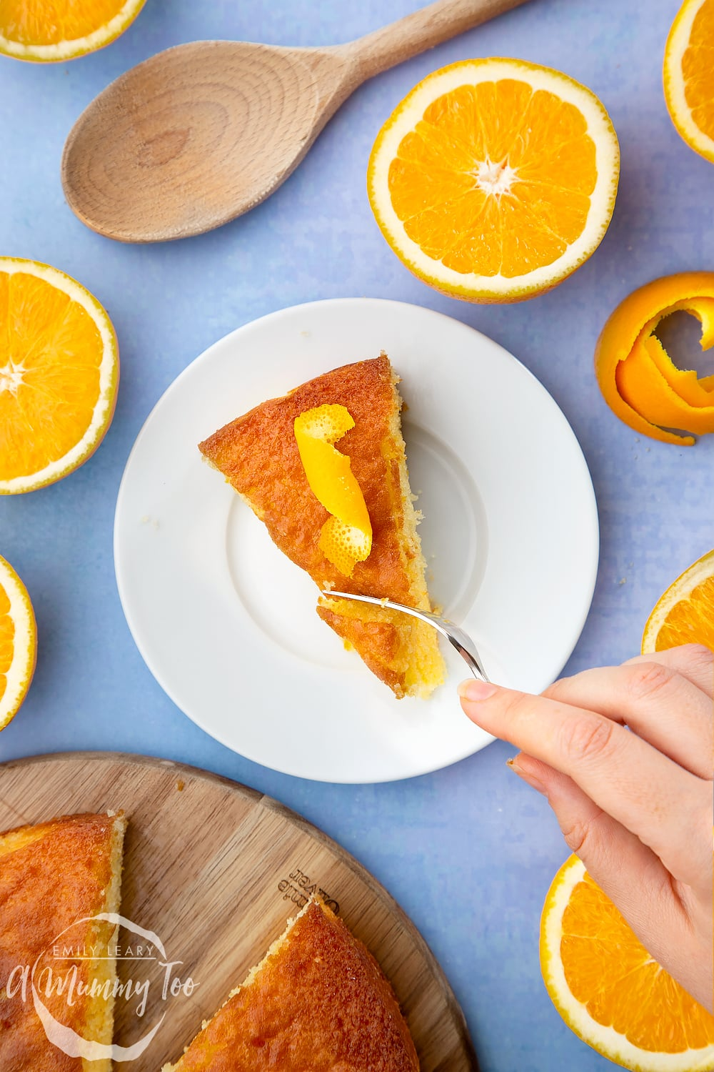 A slice of orange drizzle cake served on a small white plate. A curl of orange peel sits on top of the cake. A hand holding a cake fork cuts into the cake.