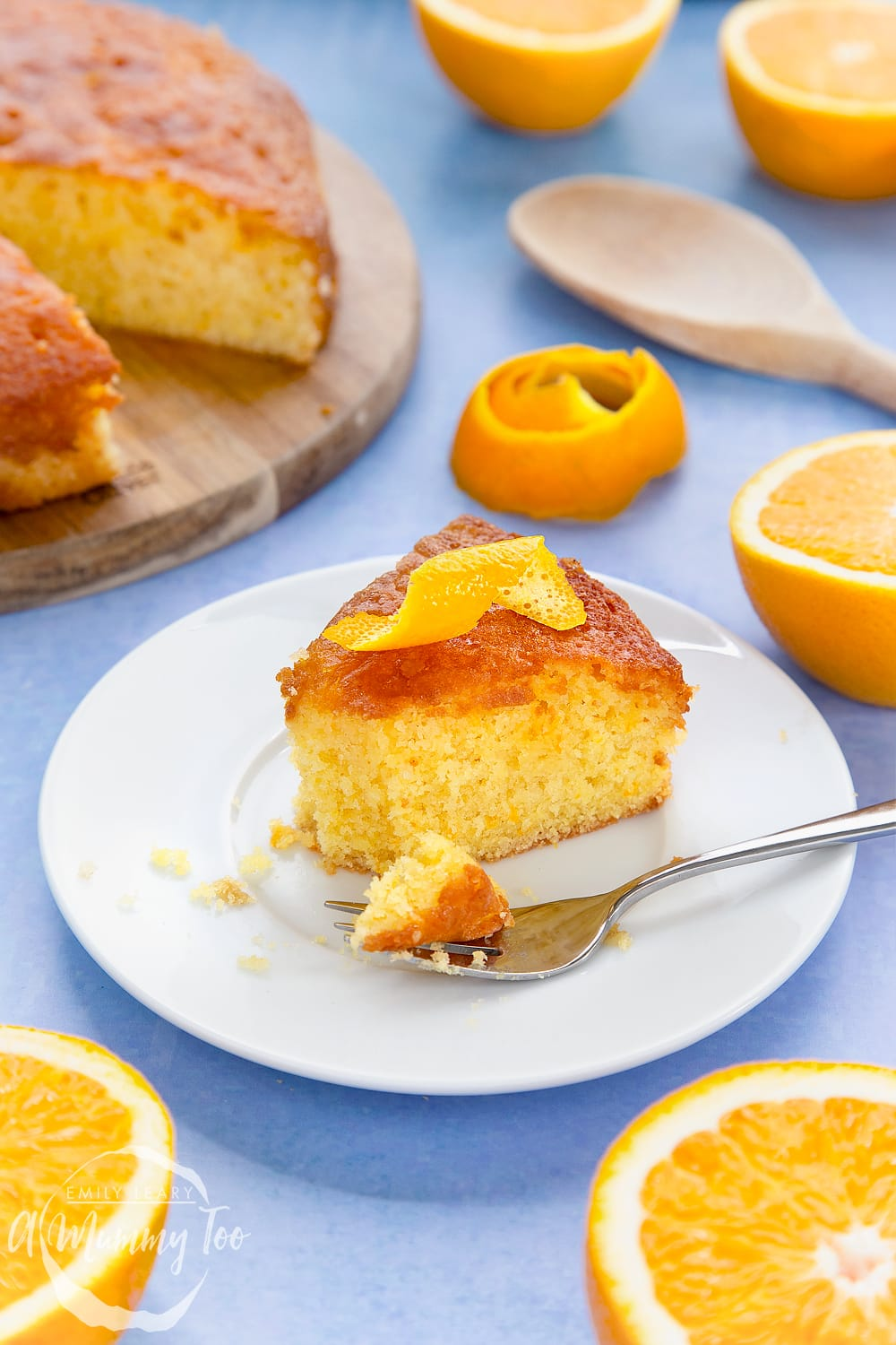 A slice of orange drizzle cake served on a small white plate. A curl of orange peel sits on top of the cake. A cake fork rests on the plate with crumbs on it.