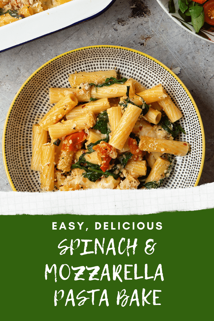 Overhead shot of a decorative bowl filled with Cherry tomato, spinach and garlic mozzarella pasta bake. At the bottom of the image there's some white text describing the image for Pinterest.
