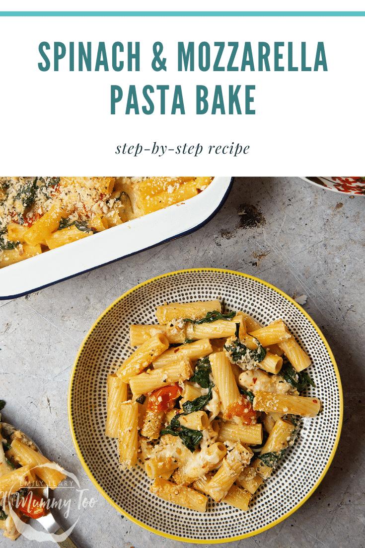 Overhead shot of a decorative bowl of Cherry tomato, spinach and garlic mozzarella pasta bake on a grey table.