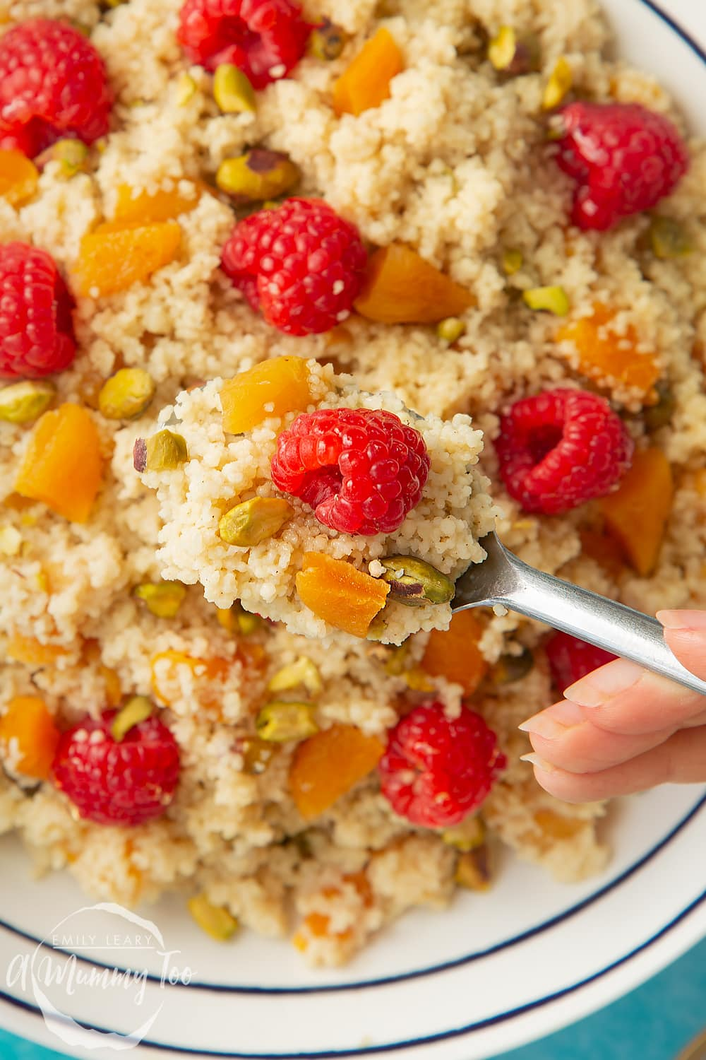Close up shot of a spoon going into the bowl of sweet breakfast couscous