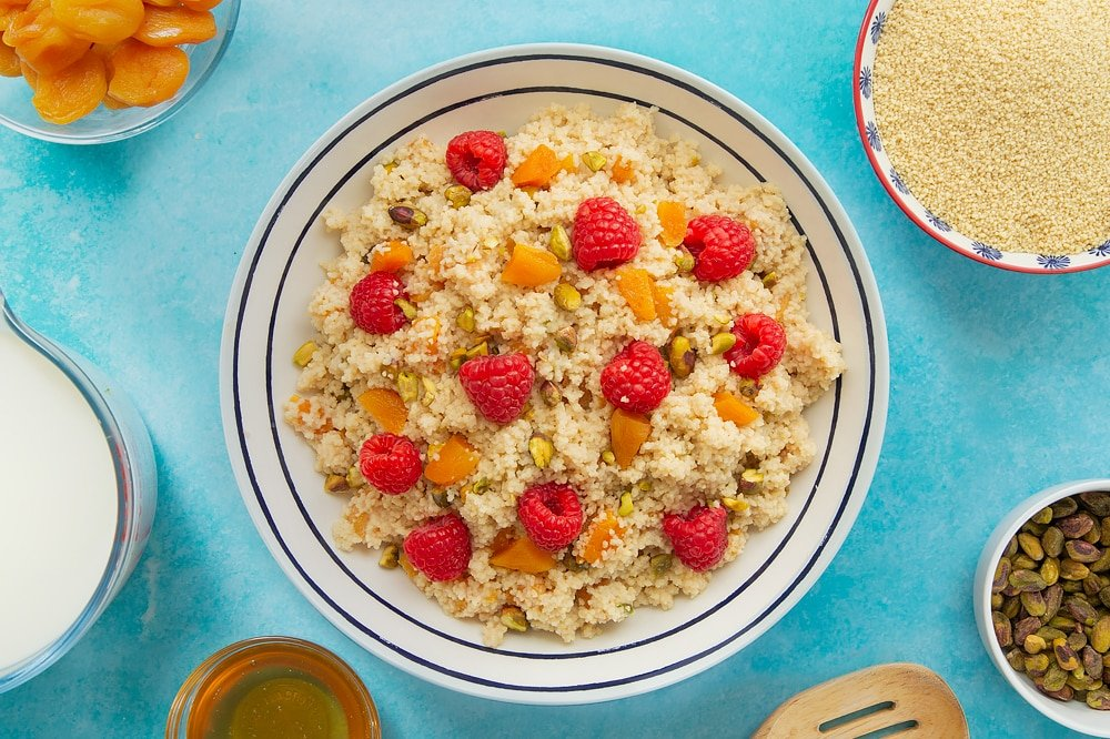 Overhead shot of the sweet breakfast couscous in a decorative black and white bowl topped with fruits.