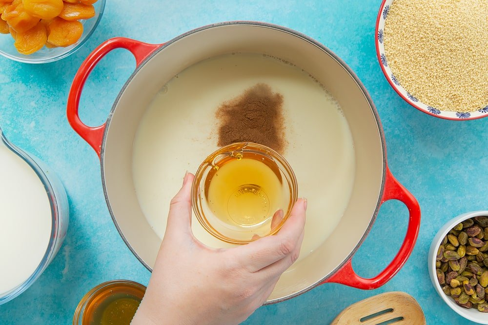Overhead shot of the honey being added to the red pan of sweet breakfast couscous ingredients.