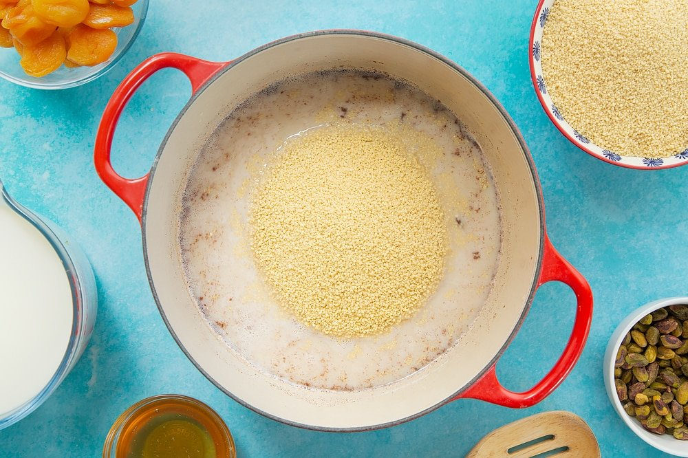 Overhead shot of adding the cous cous to the pan of ingredients. The pan sits on a blue background surrounded by additional ingredients required for the recipe.