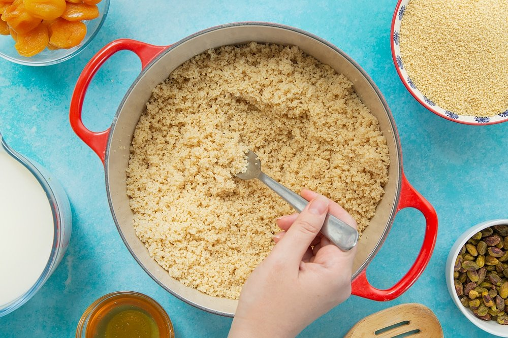 Fluffing the sweet breakfast couscous after it's been steamed with the lid on. The fluffing is being done with a fork. At the side of the pan there's additional ingredients used for this recipe.