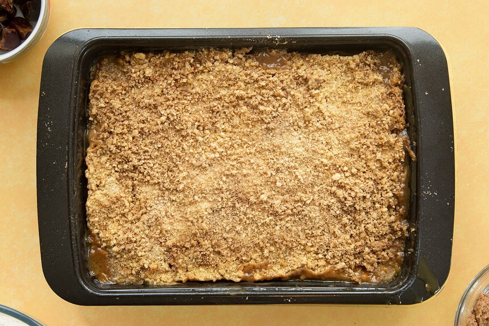 Overhead shot of the finished toffee apple crumble in a pan having been in the oven.