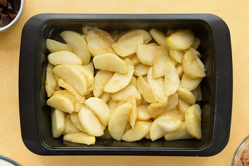 Overhead shot of a greeced oven dish filled with the apples.