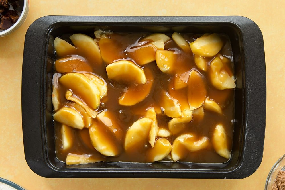 Overhead shot of the toffee being poured over the top of the apples.