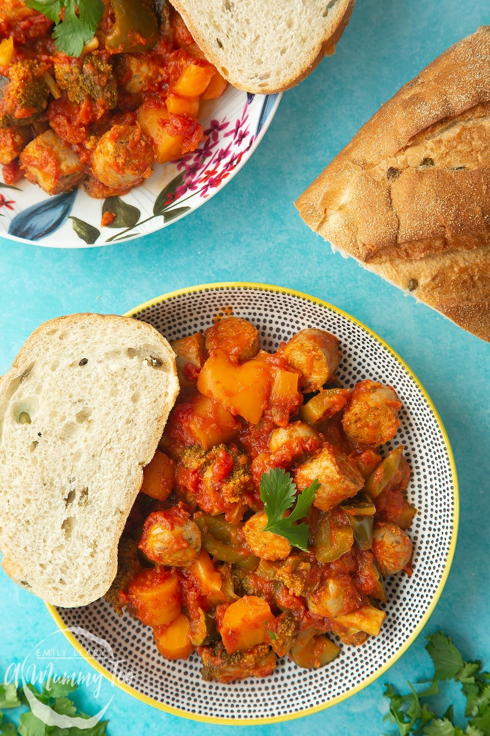 Two bowls of slow-cooked vegetarian sausage casserole on a blue background with a crusty bread roll at the side.