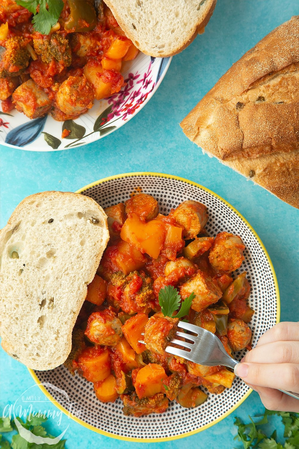Overhead shot of two decorative bowls filled with slow-cooked vegetarian sausage casserole. At the side of the bowls there's a crusty bread roll.