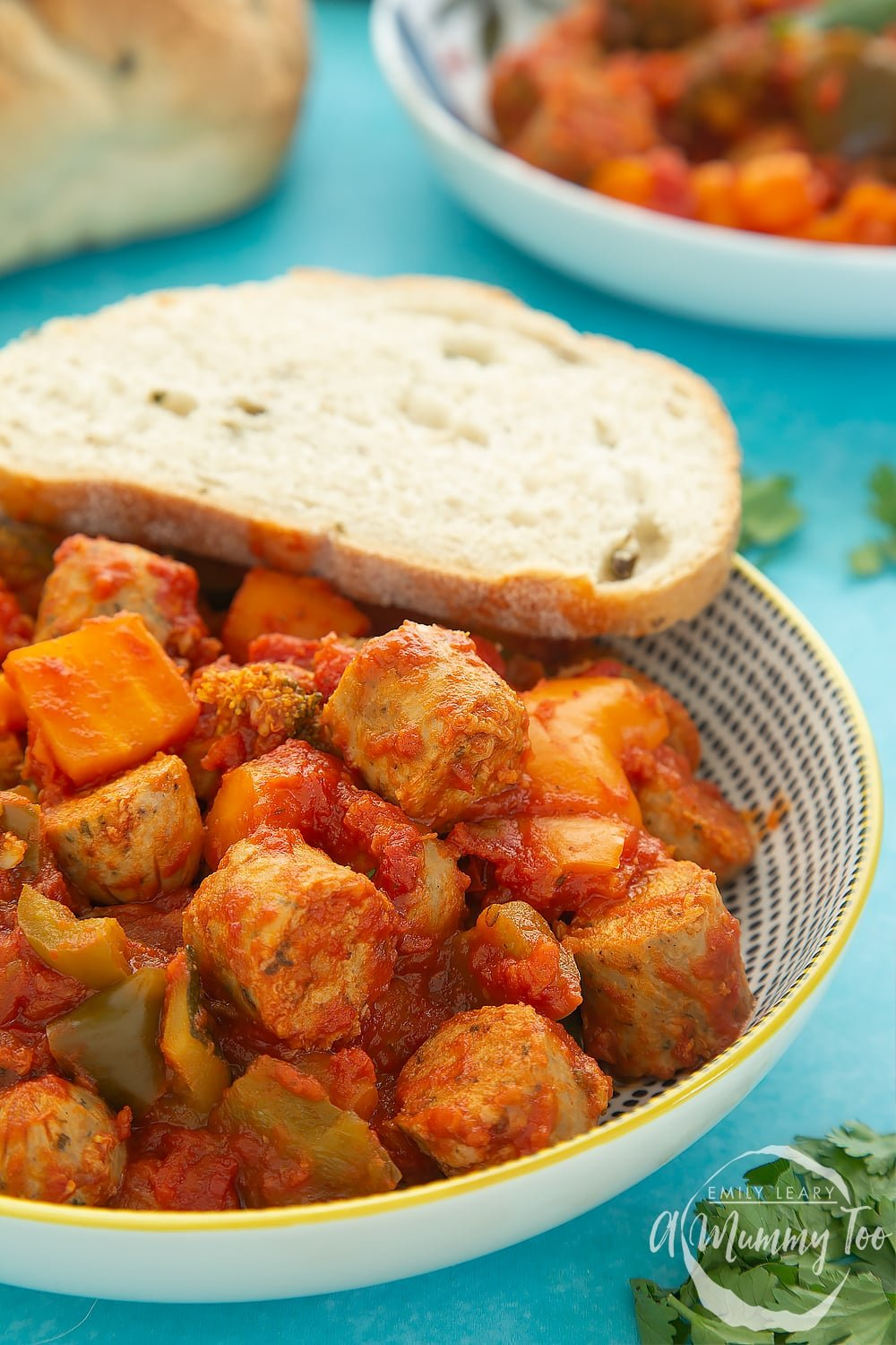 Close up of a bowl of slow-cooked vegetarian sausage casserole with a crusty bread roll on the side. The bowl sits on a blue table.