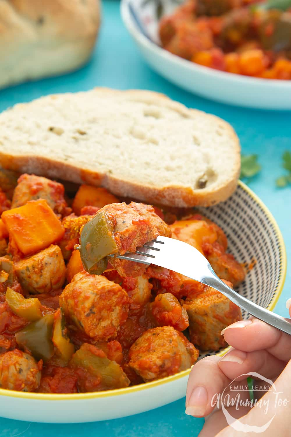 Close shot of the Slow-cooked vegetarian sausage casserole in a bowl with a crusty breadroll on the side.