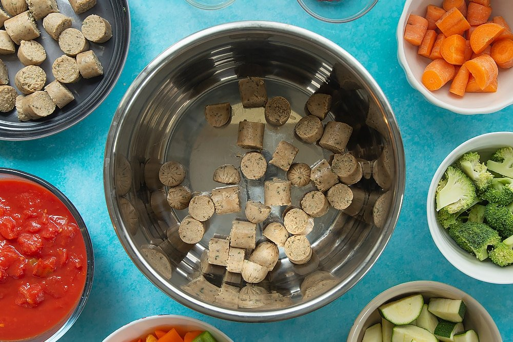 Overhead shot of chopped up sausage for the Slow-cooked vegetarian sausage casserole surrounded by other ingredients required for the meal.