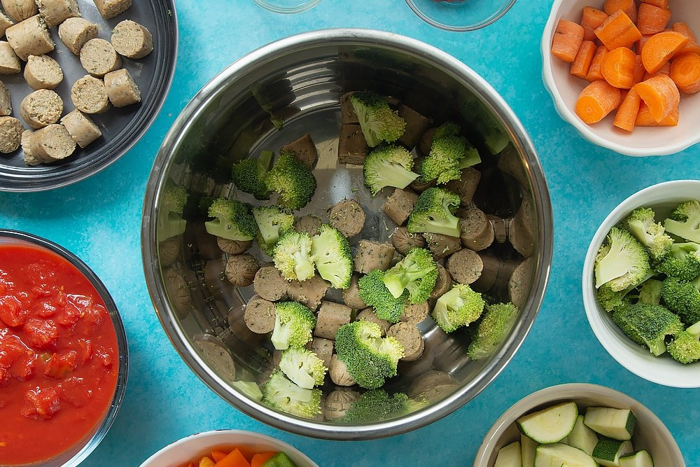 Adding the broccoli to the bowl for the slow-cooked vegetarian sausage casserole. Additional ingredients for the recipe surround the bowl.