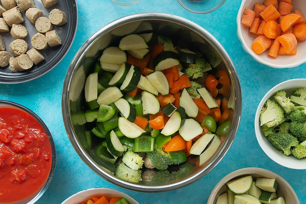 Sliced courgettes being added to the Slow-cooked vegetarian sausage casserole bowl.