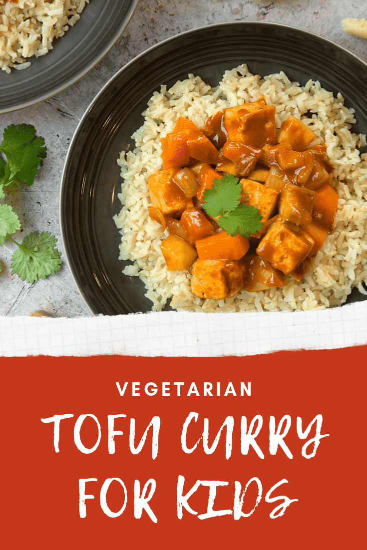 Overhead shot of tofu curry on a black plate with some white text describing the image for Pinterest.
