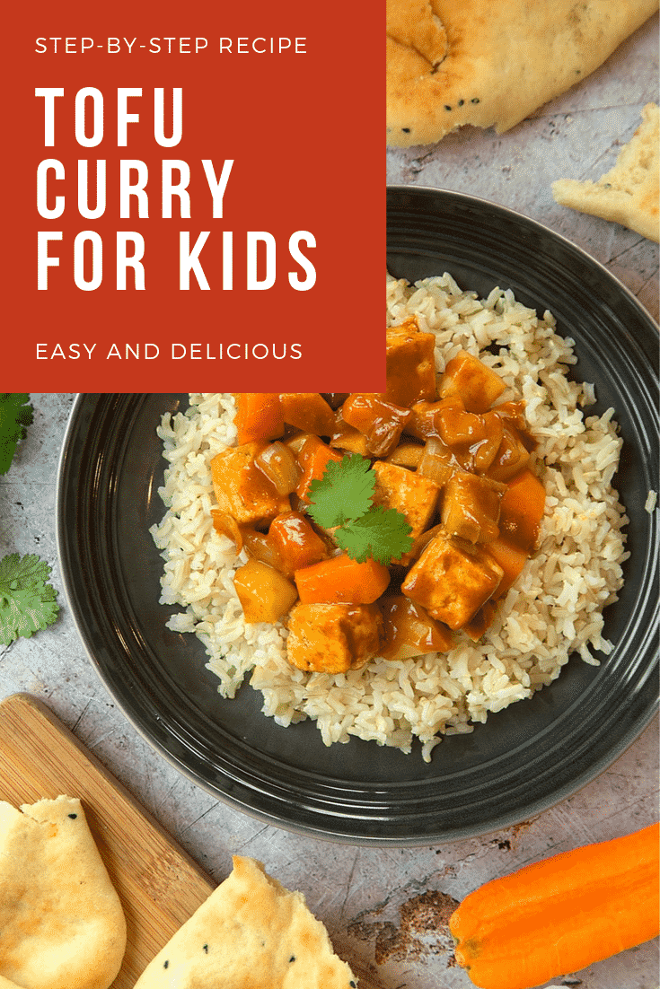 Overhead shot of the tofu curry for kids on a black plate with a fork on the side. The plate is surrounded by some additional ingredients required for the recipe. At the top of the image there's some text describing the image for Pinterest.