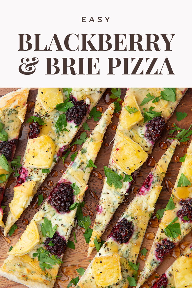 Brie and blackberry pizza sliced on a wooden board and scattered with fresh parsley and drizzled with honey. Caption reads: Easy brie & blackberry pizza.