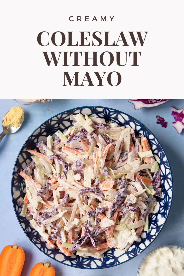 Creamy coleslaw without mayo served in a bowl. The bowl is surrounded by vegetables and creme fraiche. Caption reads: creamy coleslaw without mayo.