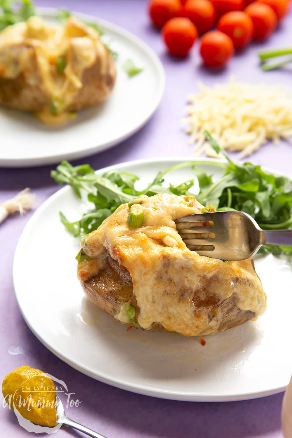 A cheese and onion jacket potato served on a white plate with rocket. A fork digs into the potato.