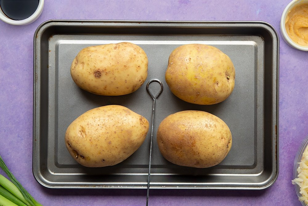 Uncooked jacket potatoes on a tray with a skewer. Ingredients to make cheese and onion jacket potatoes surround the tray.
