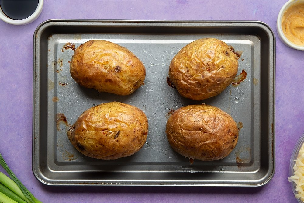 Baked jacket potatoes on a tray. Ingredients to make cheese and onion jacket potatoes surround the tray.