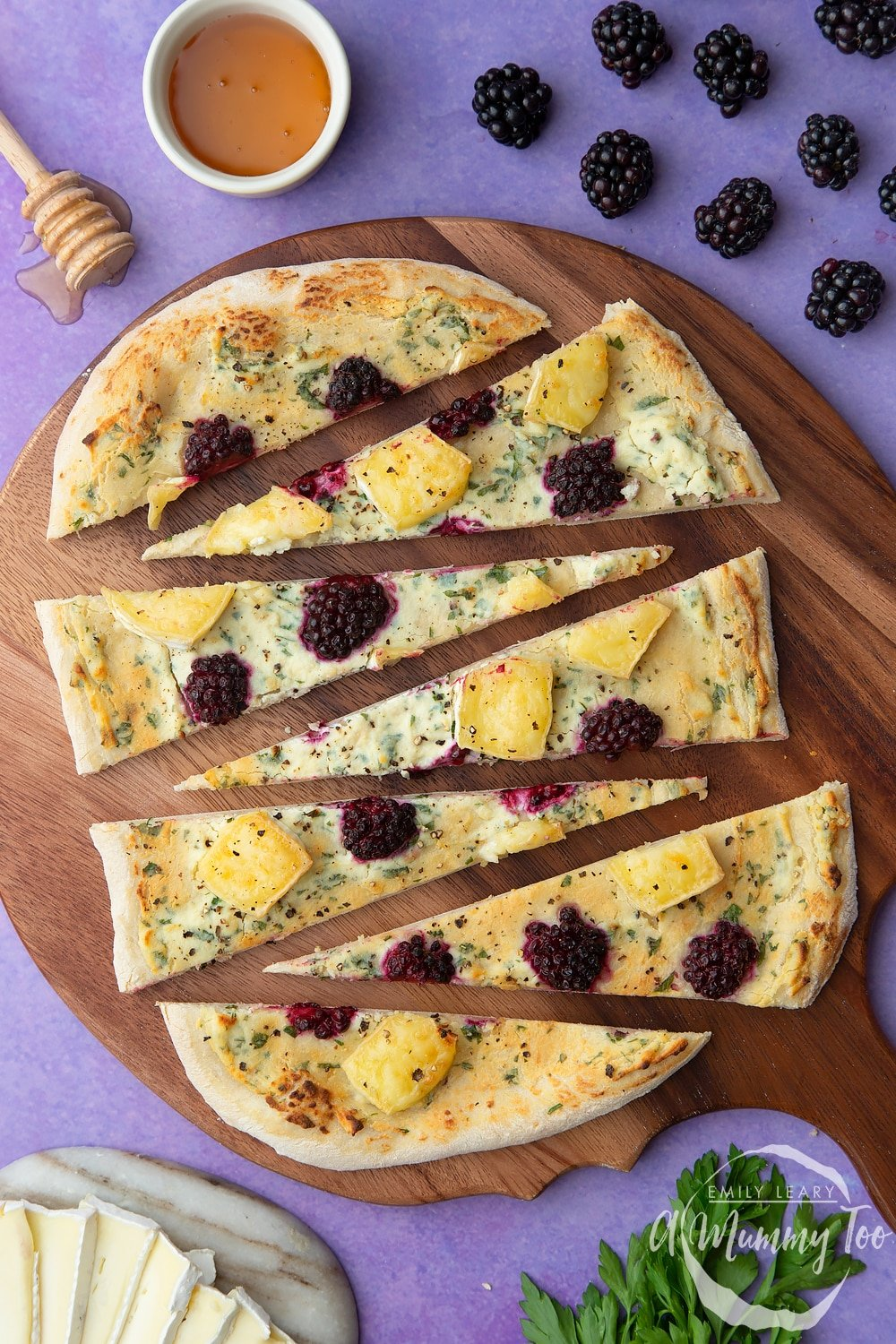 Brie and blackberry pizza sliced on a wooden board. Ingredients surround the board.