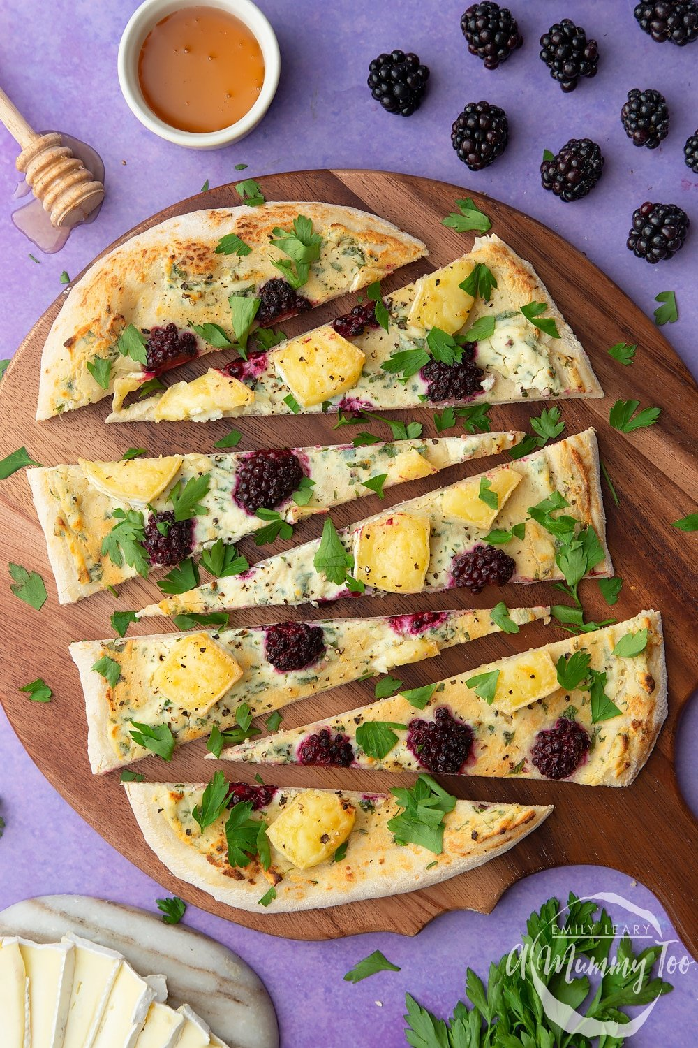 Brie and blackberry pizza sliced on a wooden board and scattered with fresh parsley. Ingredients surround the board.