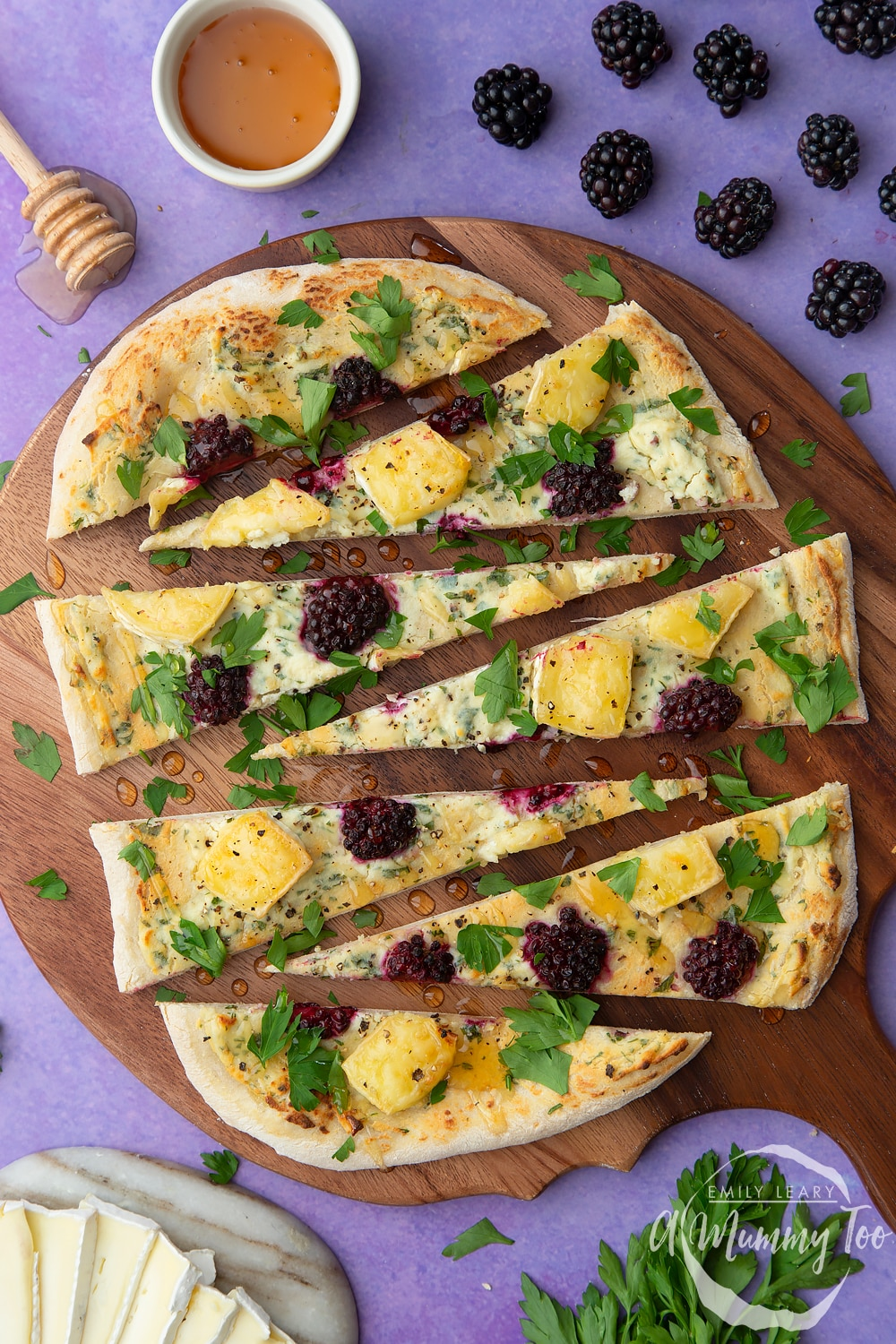 Brie and blackberry pizza sliced on a dark wooden board.
