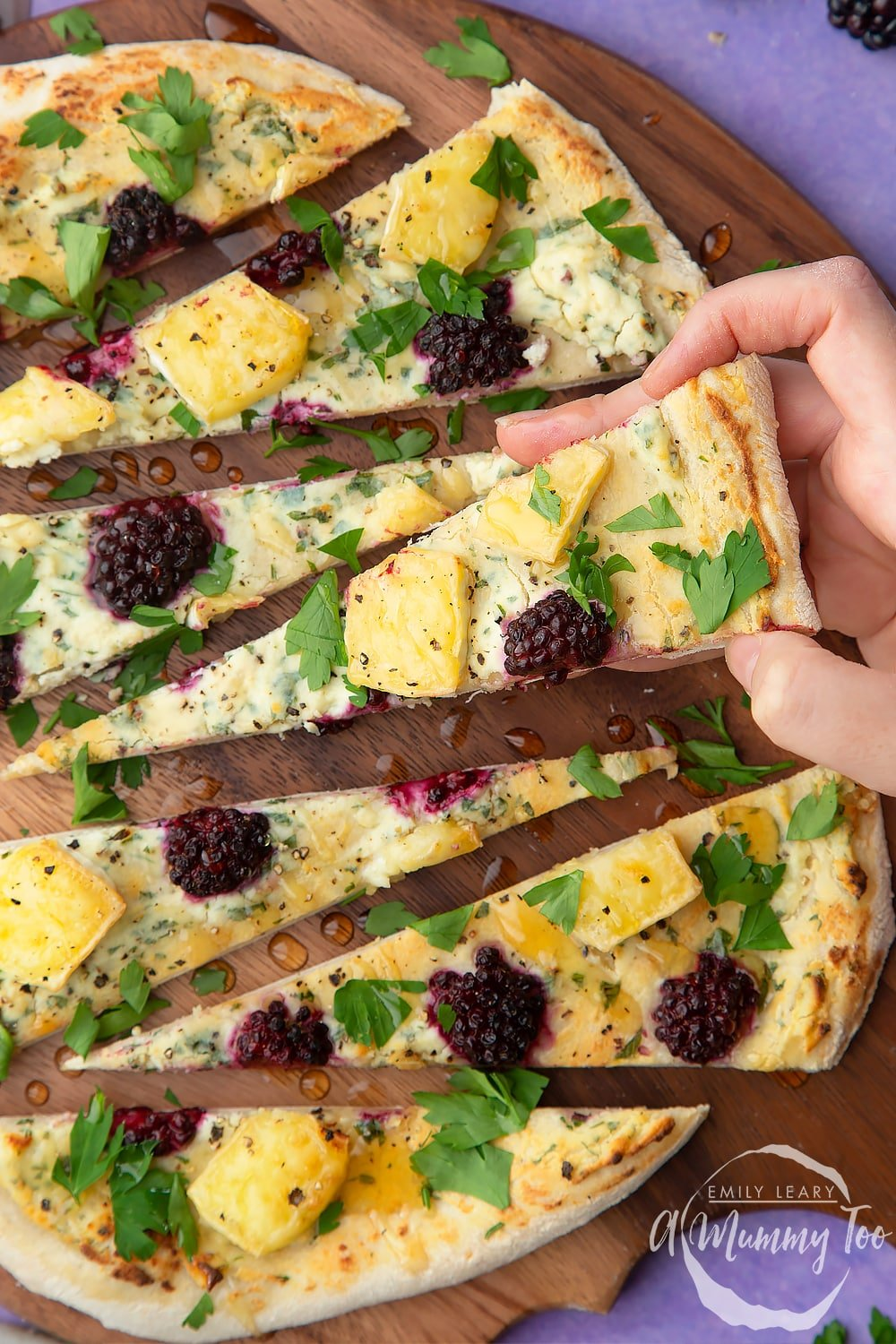 A hand picking up a slice of brie and blackberry pizza on a dark wooden board.