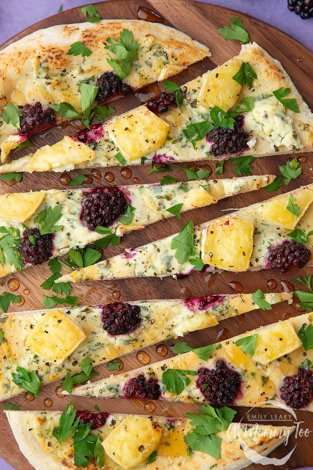 Brie and blackberry pizza sliced on a dark wooden board. The pizza has been drizzled with honey.