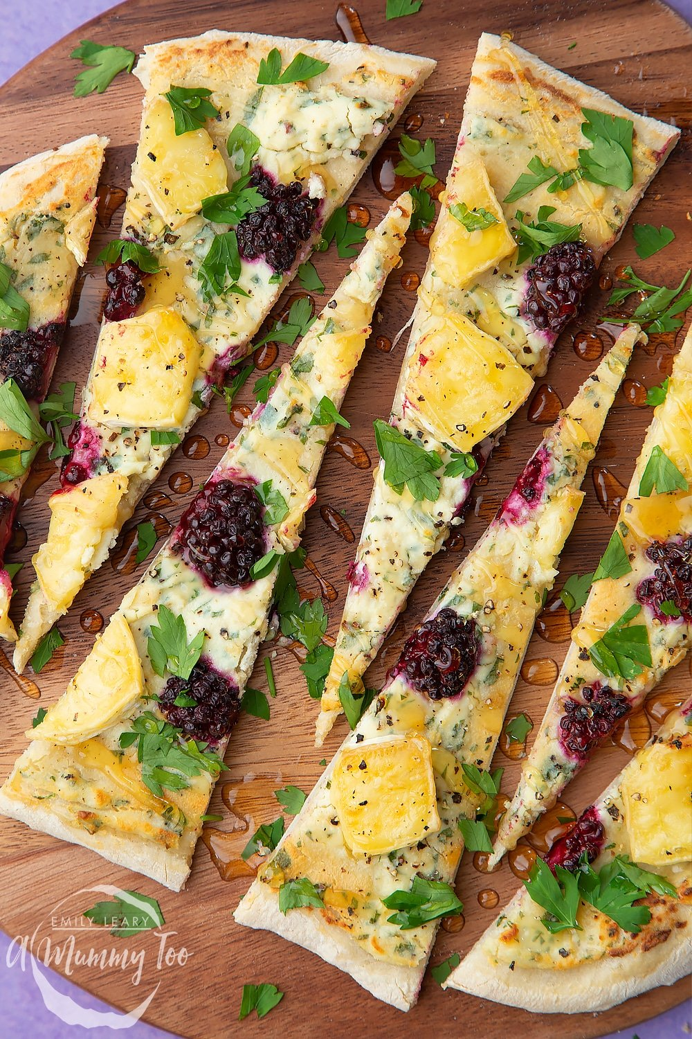 Brie and blackberry pizza sliced on a dark wooden board. The slices are long and thin.