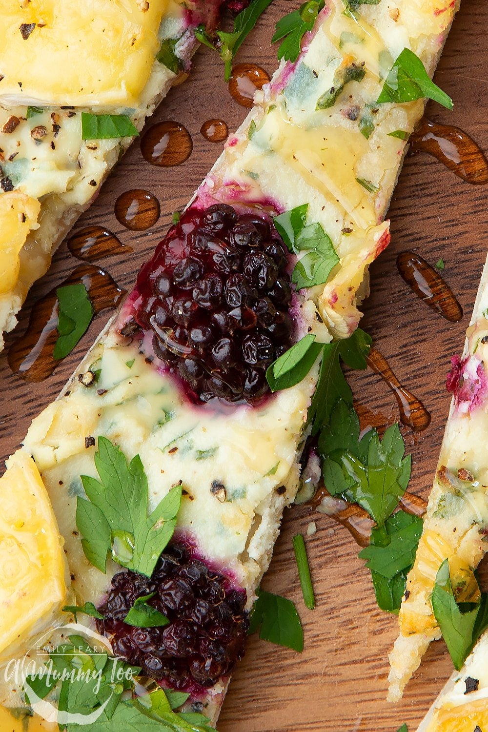 Closeup of a brie and blackberry pizza, sliced on a dark wooden board.