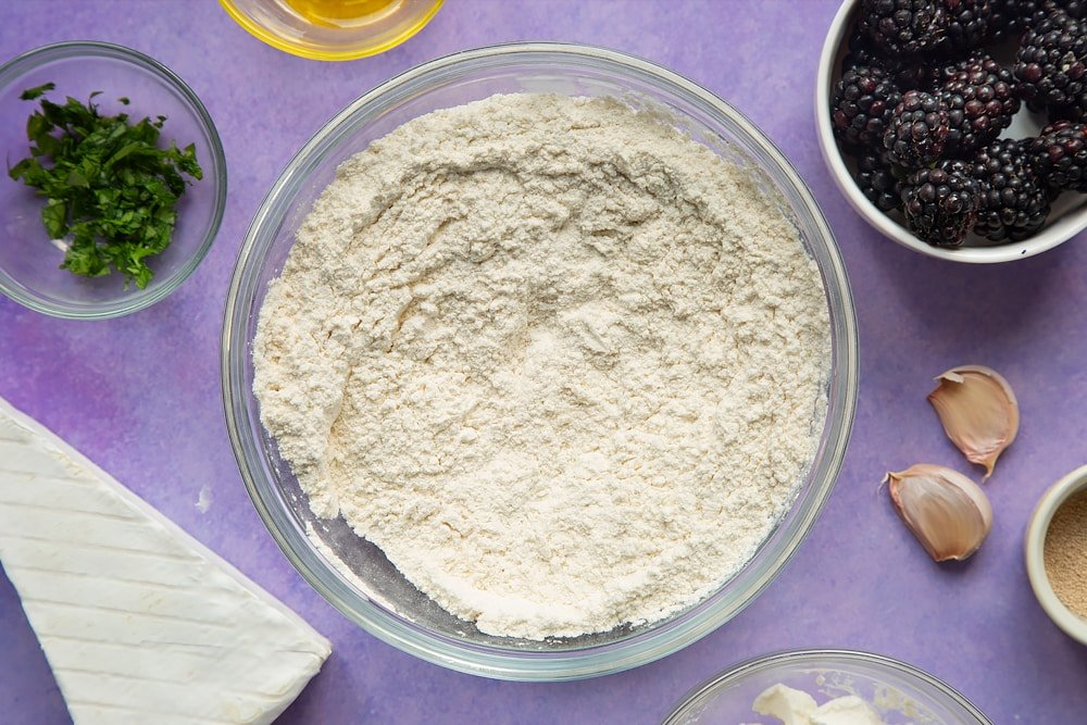 Flour, yeast and salt mixed together in a glass mixing bowl. Ingredients for brie and blackberry pizza surround the bowl.
