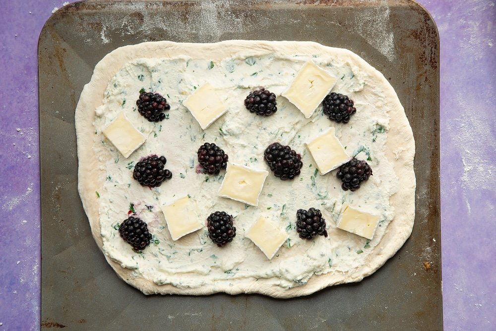 An oblong of pizza base on a baking sheet, spread with the ricotta mix and topped with blackberries and slices of brie.