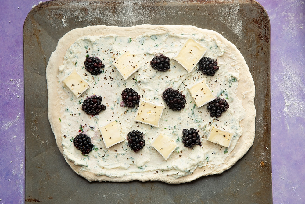 An oblong of pizza base on a baking sheet, spread with the ricotta mix and topped with blackberries and slices of brie. Seasoned with black pepper.