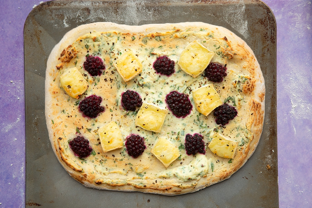 A freshly baked brie and blackberry pizza with a golden crust on a baking sheet.