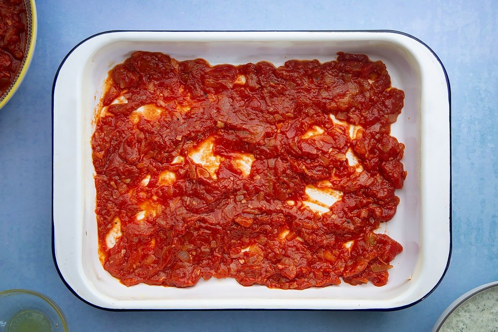Overhead shot of tomato layer in a lasagne dish