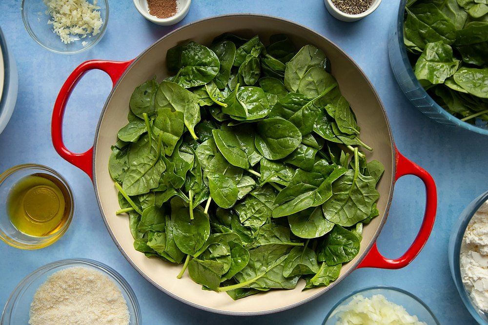 Overhead shot of spinach in a red pan