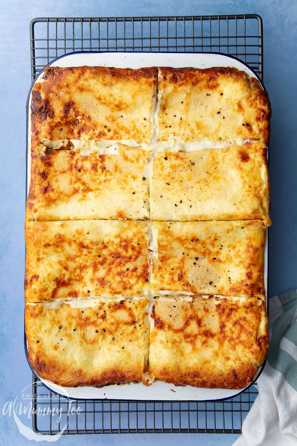 Overhead shot of parted baked Butternut squash and ricotta lasagne in a lasagne dish with a mummy too logo in the lower-left corner