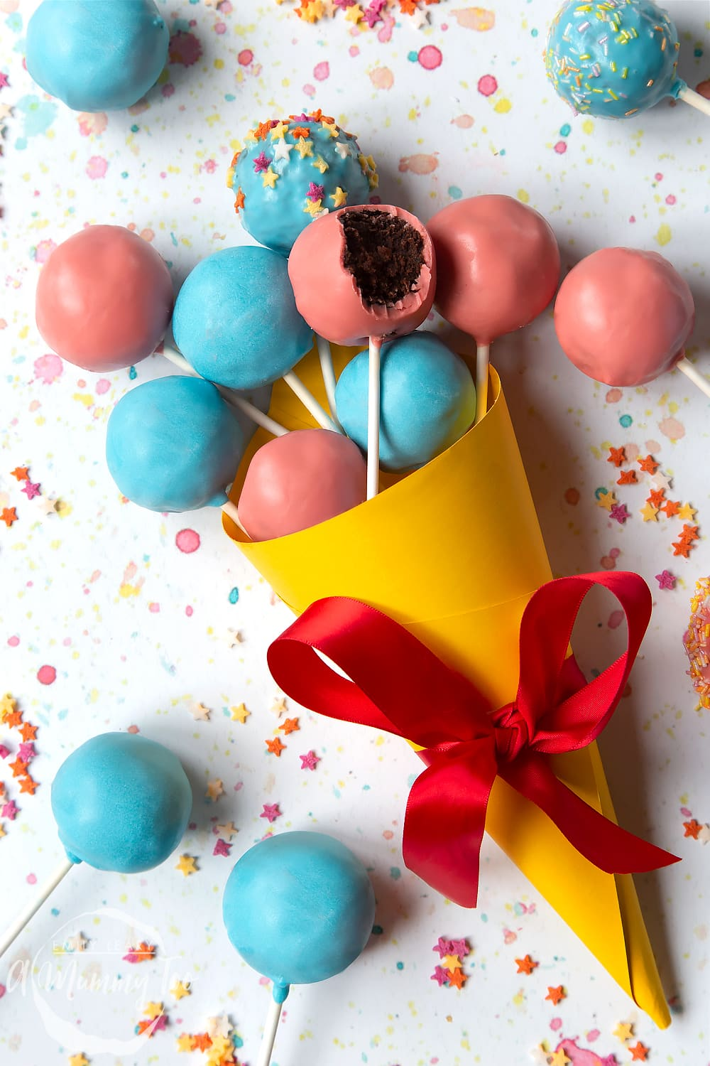 A cake pop bouquet surrounded by other cake pops. The bouquet is made from several blue and pink cake pops, gathered together and wrapped in a yellow paper cone with a red ribbon.