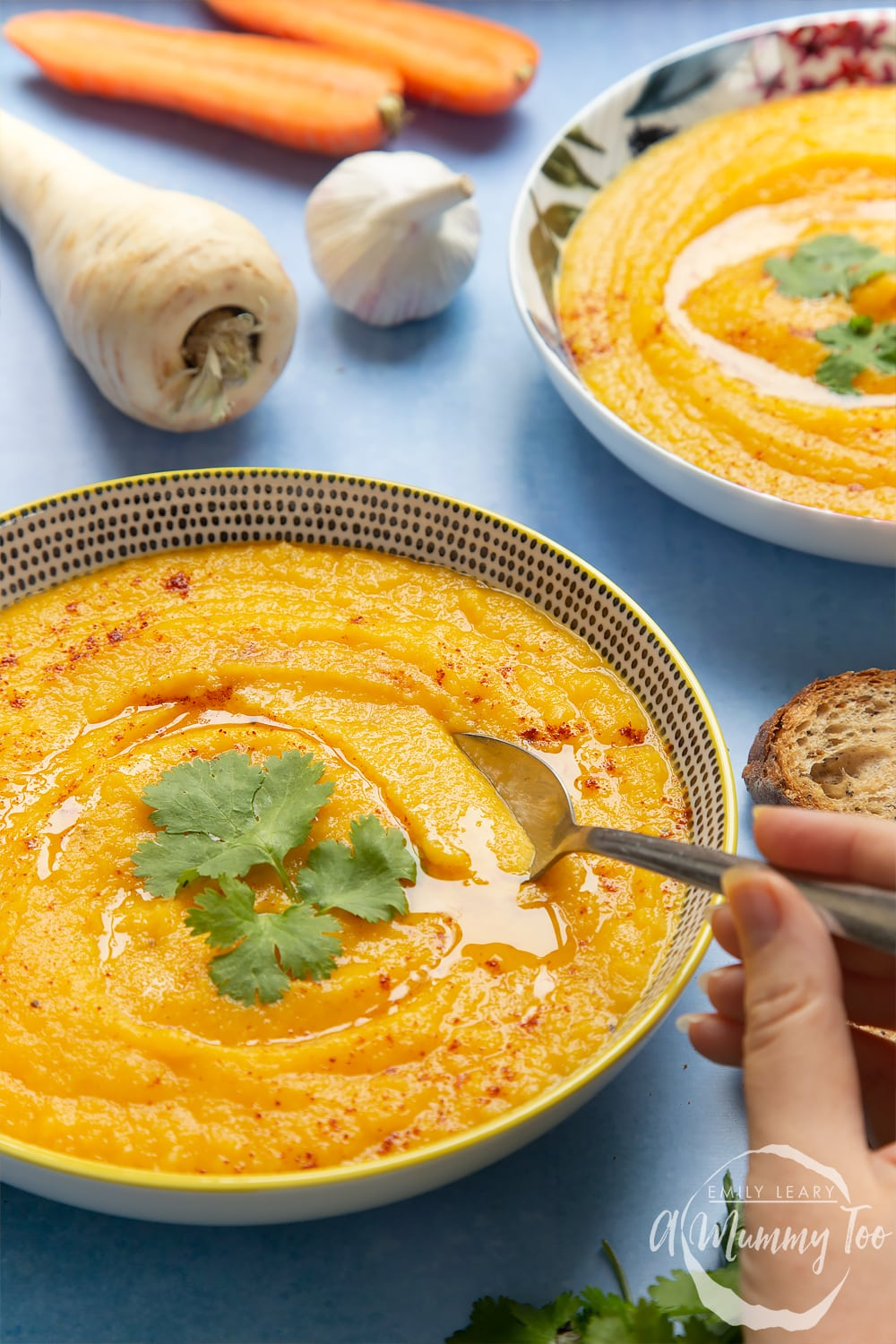 Two bowls of carrot and parsnip soup. A hand holding a spoon is going into one of the bowls. The sides are decorated with ingredients used in the carrot and parsnip soup recipe.