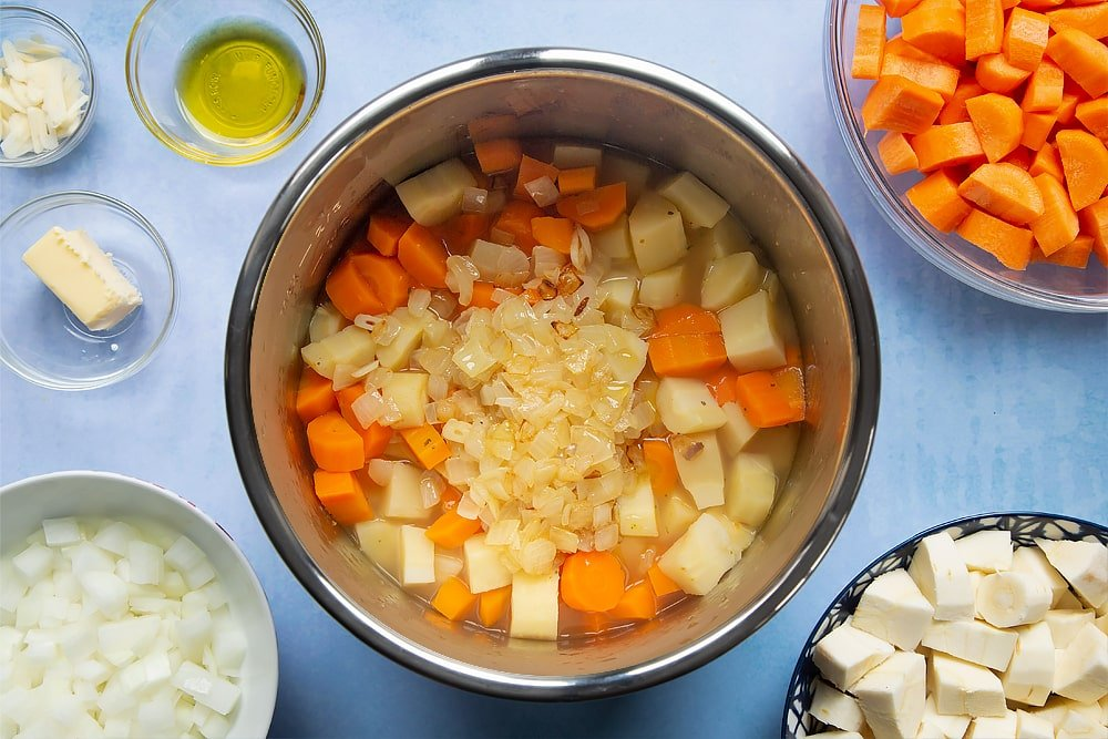Adding the fried onions and garlic to the pan of slow cooked parsnips and carrots.
